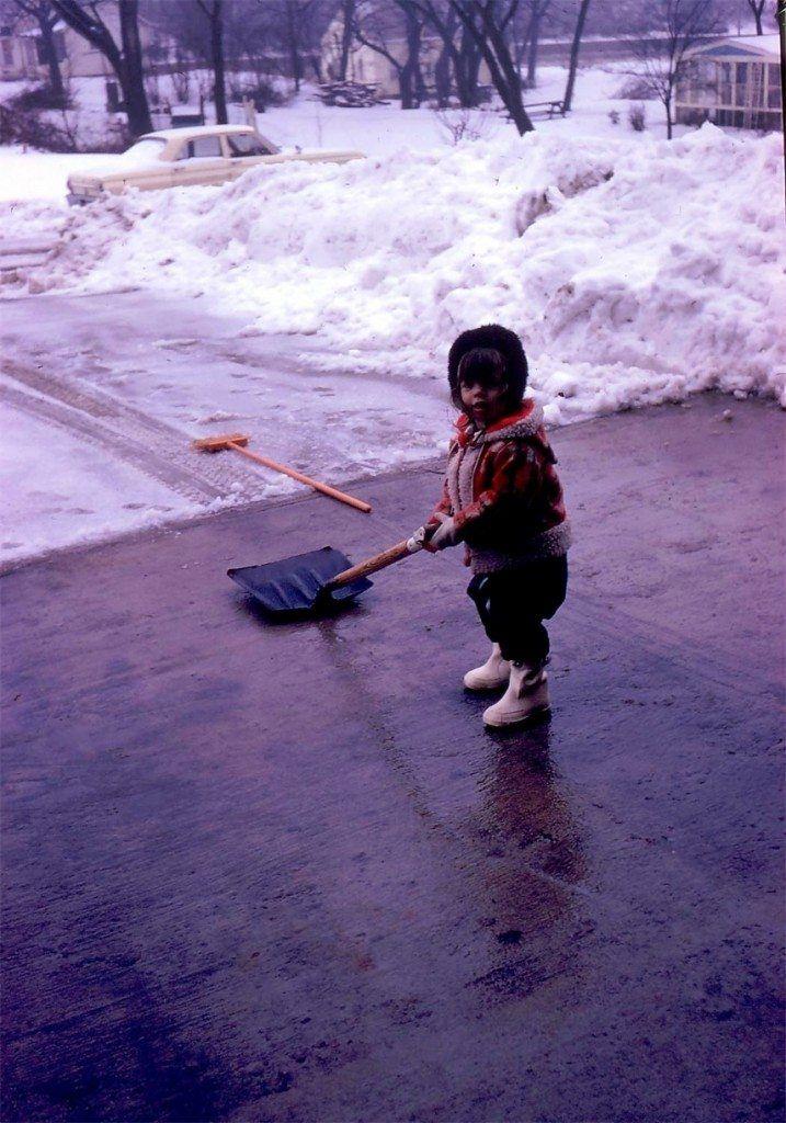 little girl shoveling snow in winter