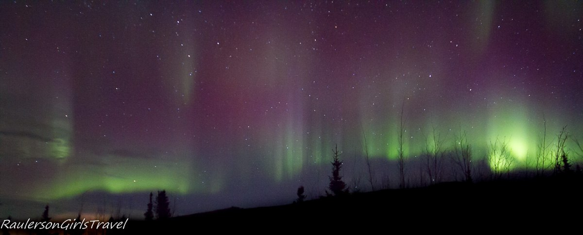 bright green and purple northern lights streaking up the sky