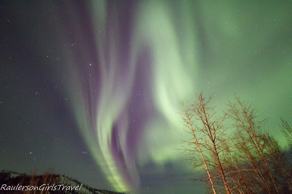 Green and purple Northern Lights display shaped like a ghost