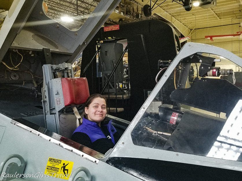 Kayla siting in a fighter jet cockpit at the Air Zoo Museum