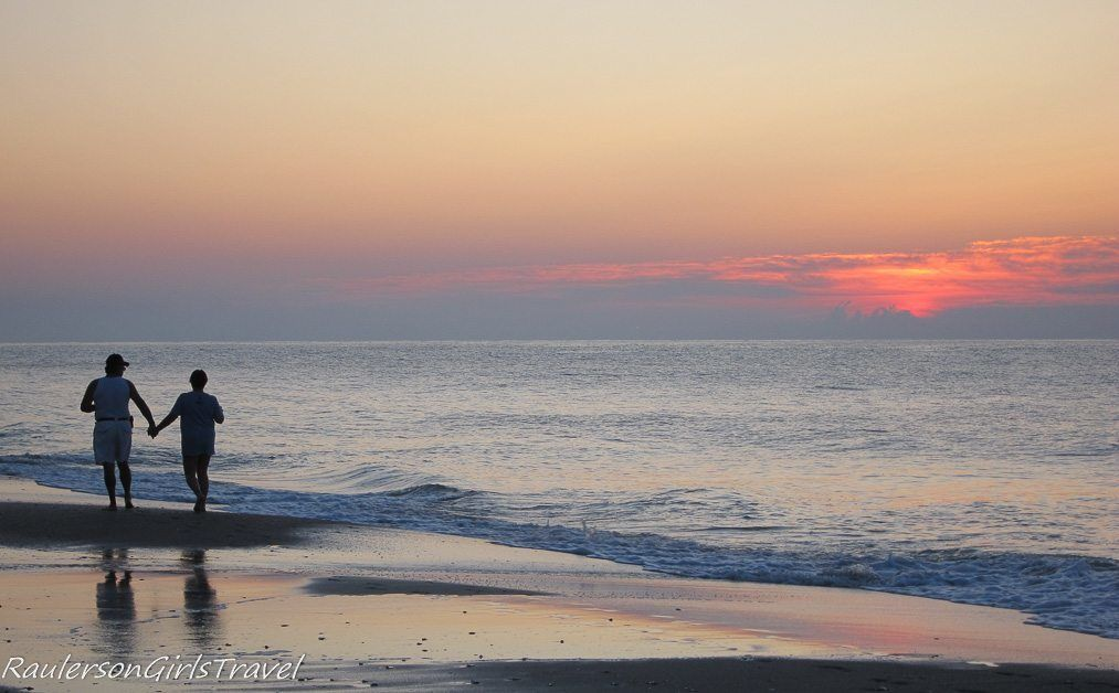Couple holding hands walking on Myrtle Beach