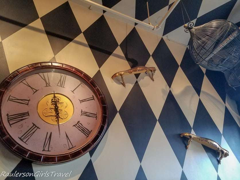 Writing desk, clock, and bird cage decorations at Mad Hatter Bistro