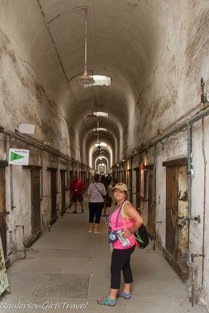 Kayla exploring the abandoned jail cells at Eastern State Penitentiary - Summer Road Trip Packing List