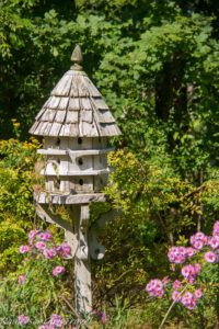 Large wooden birdhouse with pink flowers