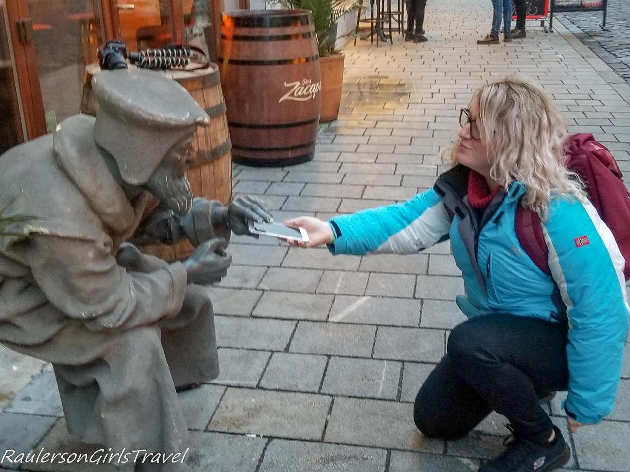 Rebecca offering her phone to a Bratislava statue