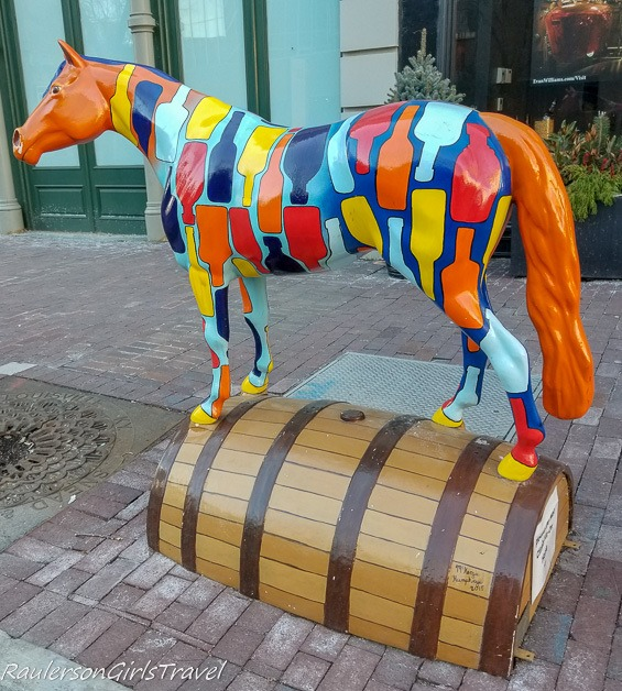 Horse statue painted with bourbon bottles standing on a keg
