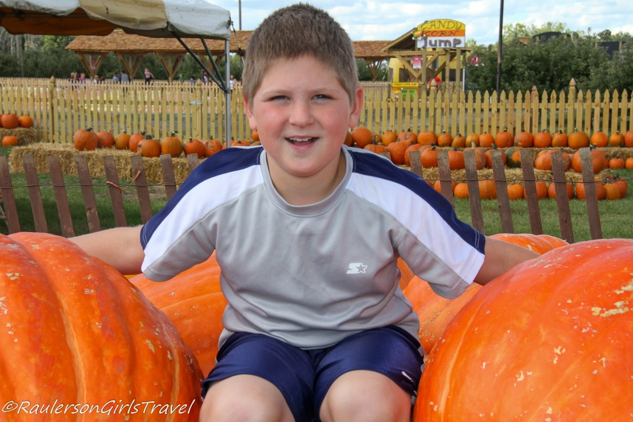 Alex sitting on large pumpkins at Blake's Cider Mill