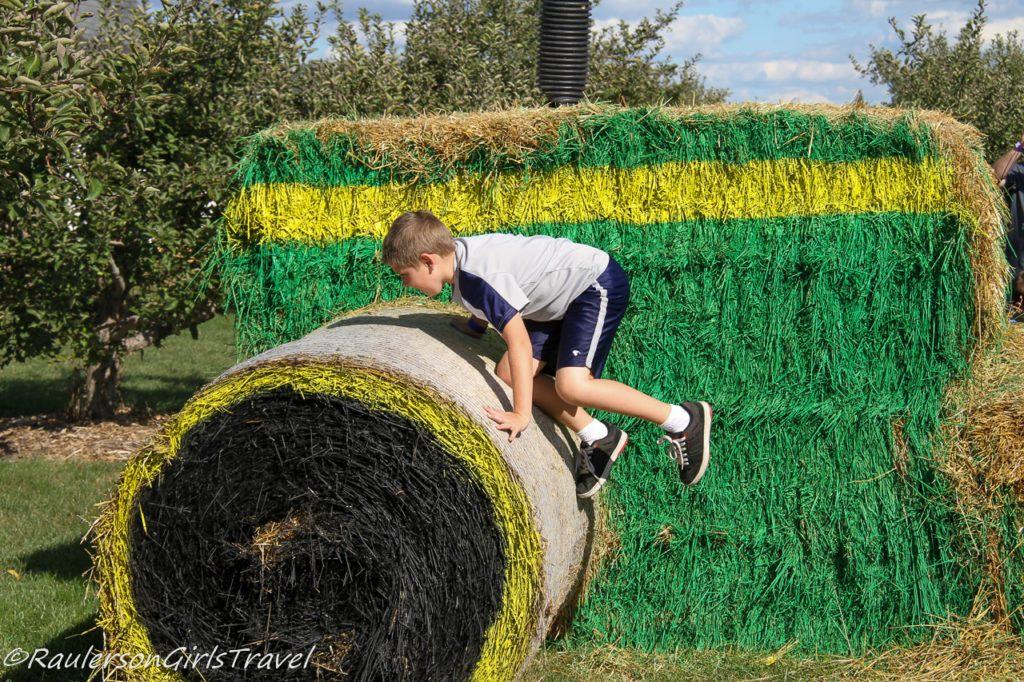 Alex climbing hay stacks at Blake's Cider Mill