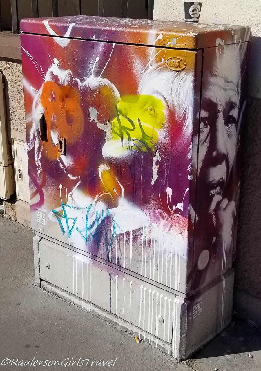 Colorful splashes and face on an electrical box in Strasbourg