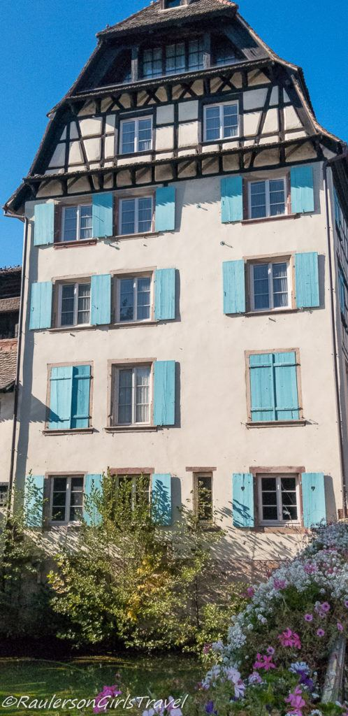 Timber-framed house with blue shutters in Strasbourg, France