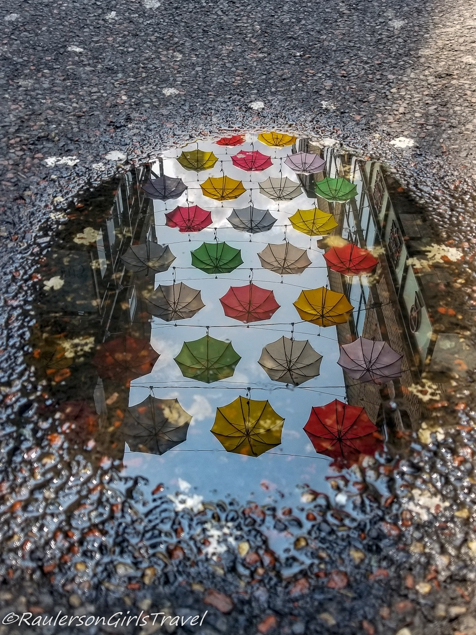 Colorful umbrella reflections in a puddle