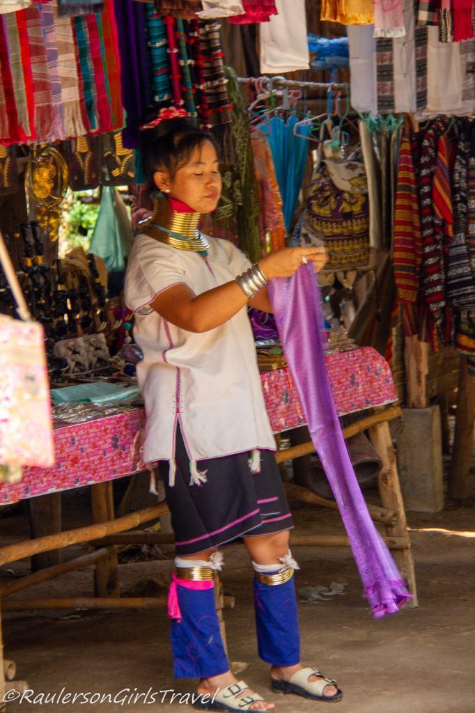 Kayan woman folding a scarf