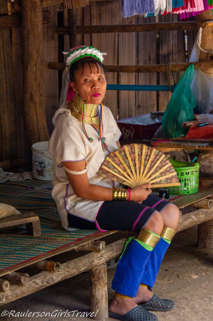 Long Neck Tribe lady sitting with fan