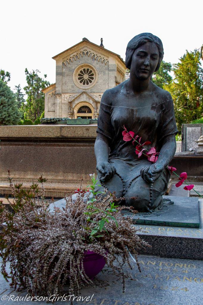 Girl kneeling looking at grave