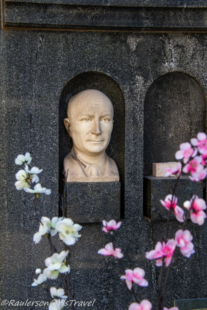 Head bust in niche with orchids