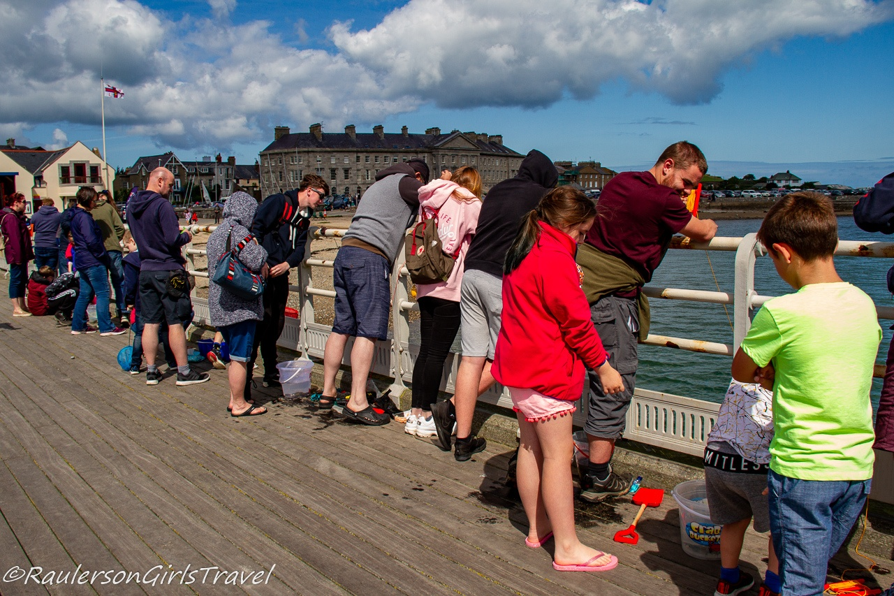 People lined up crabbing on Beaumaris Pier