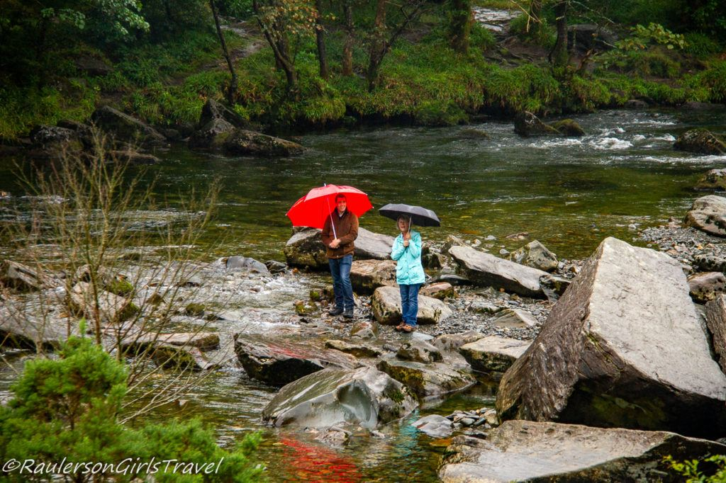 Man and a woman with umbrellas by the creek