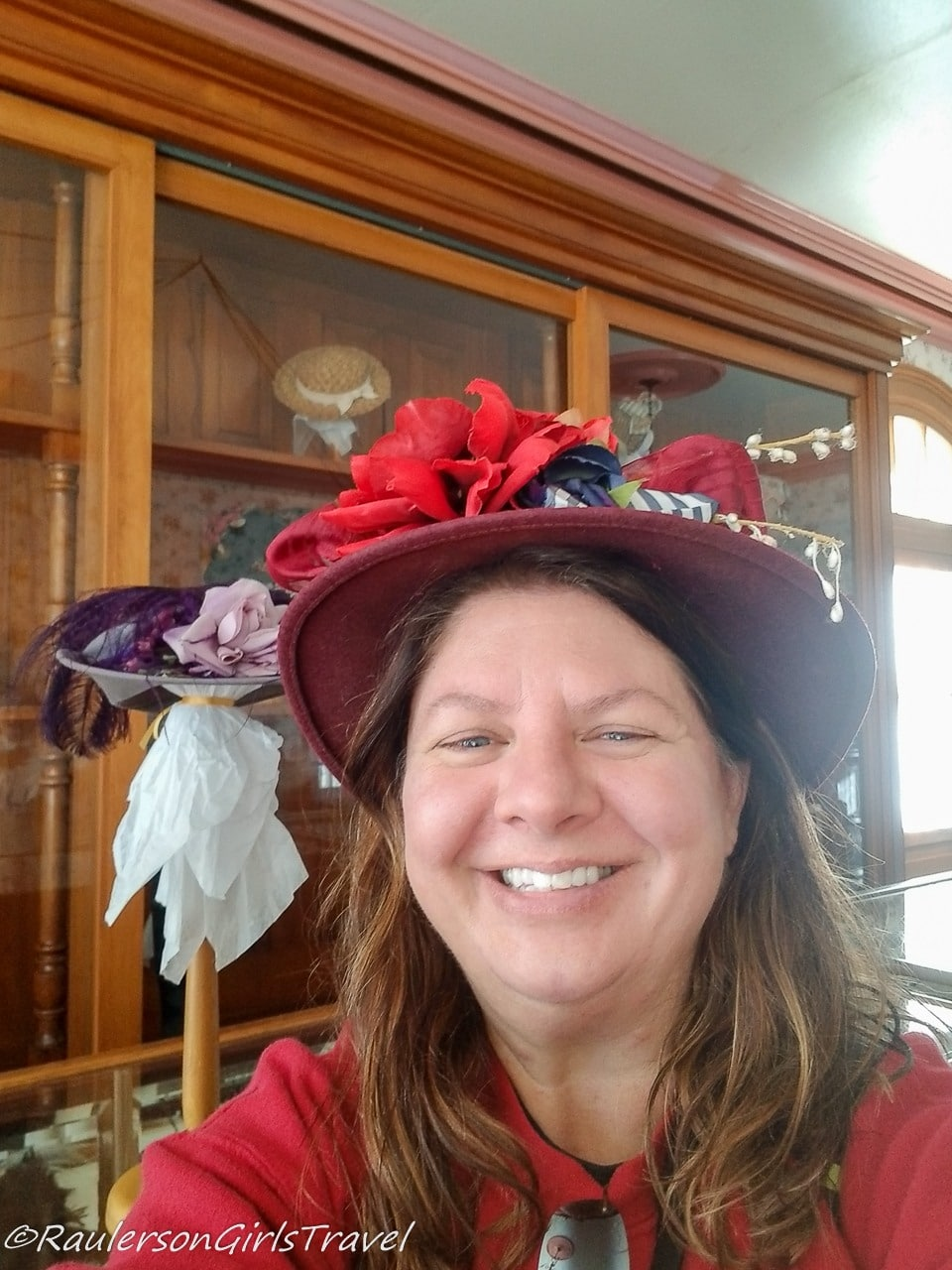 Heather trying on hats at Greenfield Village