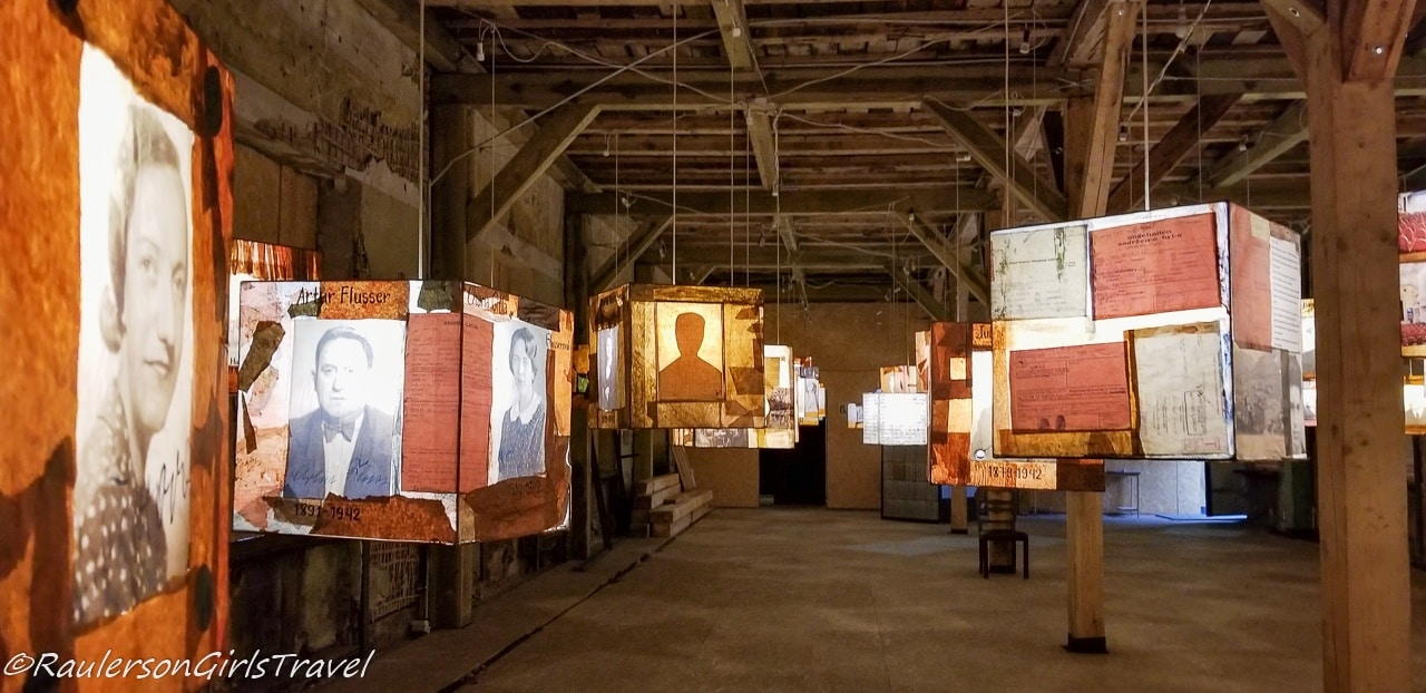 Boxes hanging from the ceiling with Jewish Latvian stories and photos on them