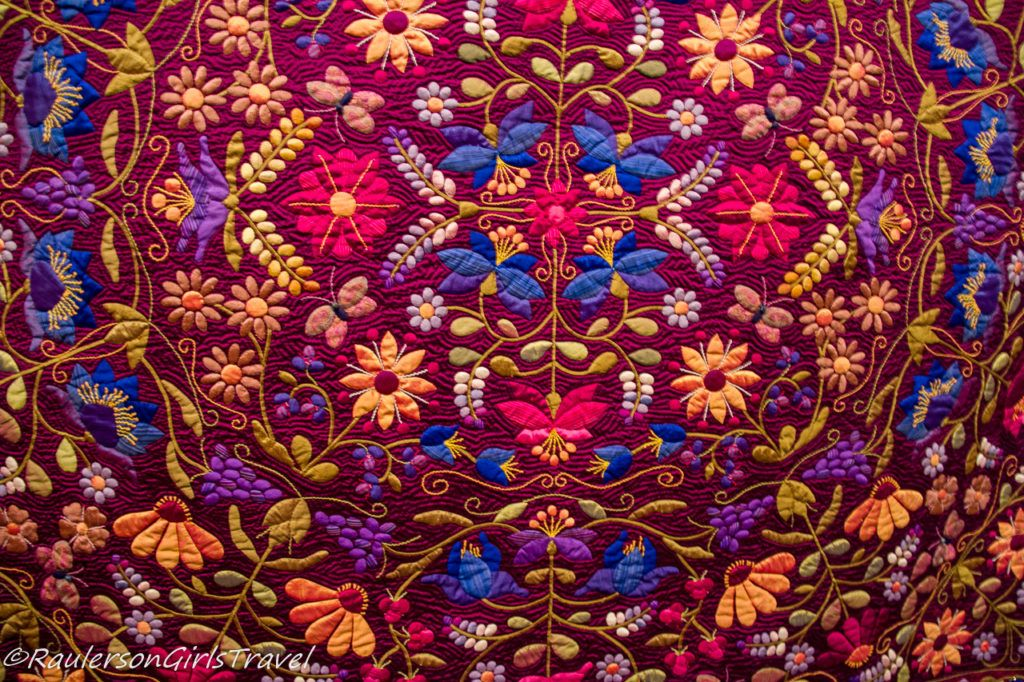 Close-up details on a hand-quilted colorful jeweled quilt