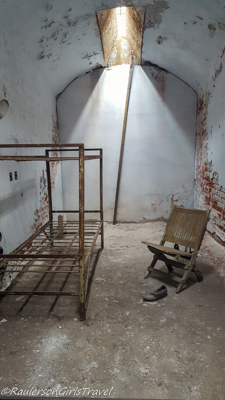 Bed frame, chair, and shoe in old jail cell