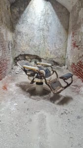Old dentist chair in an abandoned jail cell