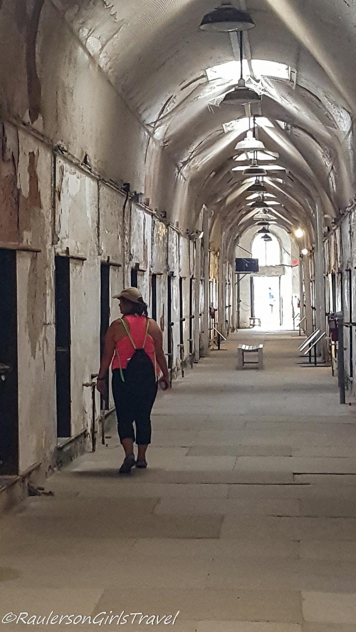 Kayla walking through an empty cell block