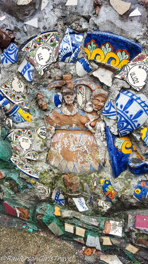 Broken pottery around a figurine displayed in a wall
