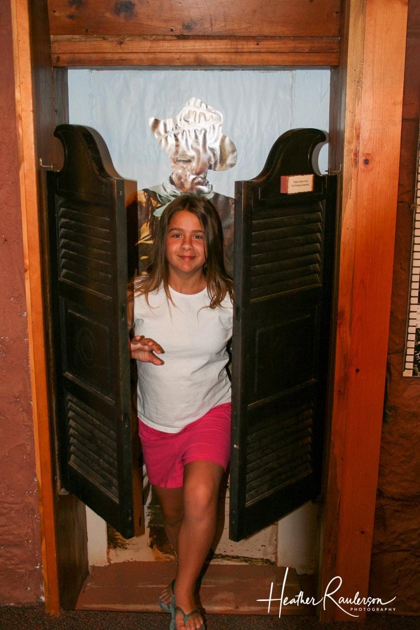 Kayla walking through western swinging doors in Goulding's Museum