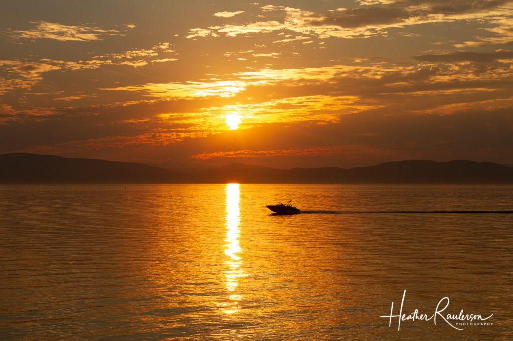 Boat cruising on Lake Champlain at sunset