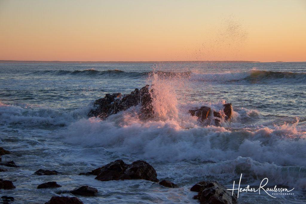 Ocean waves crashing into a rock at sunrise