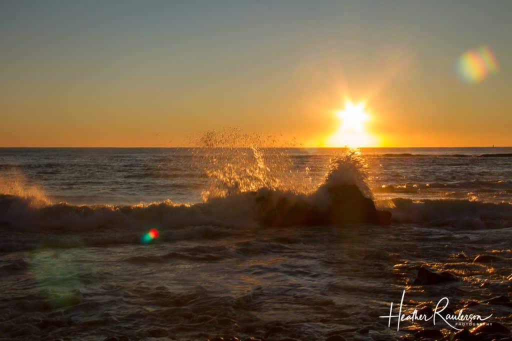 Ocean Waves crashing into rocks as the sun rises