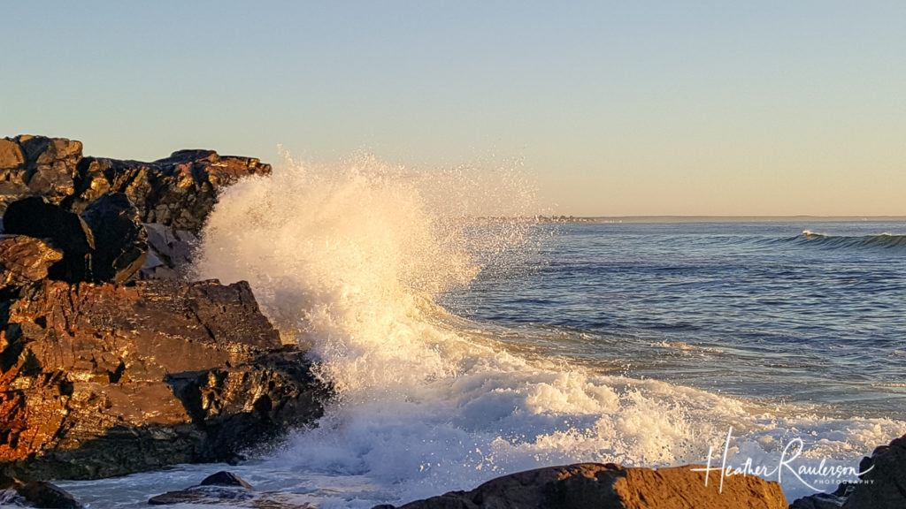 Wave crashing into rocks with sunlight in Maine