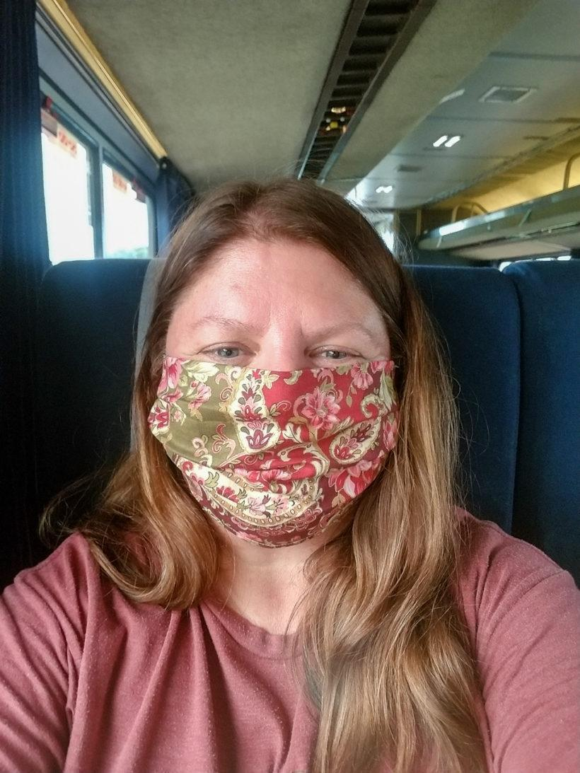 Heather wearing a mask on the Amtrak train