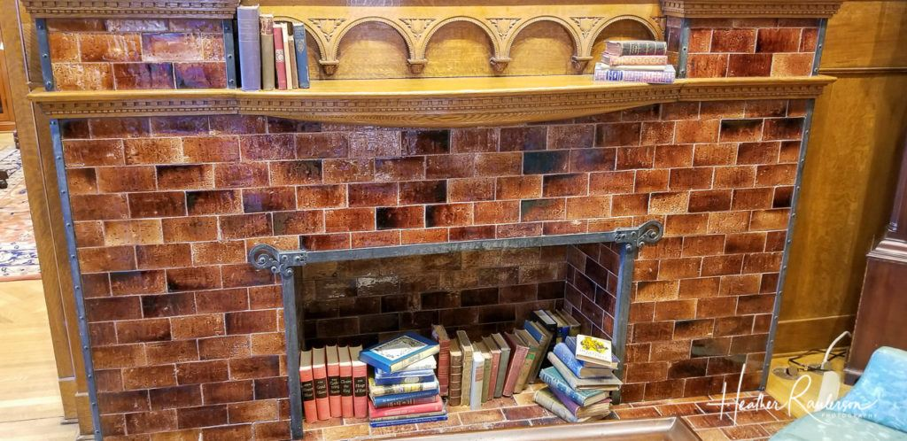 Books stacked in the fireplace in Oakhurst